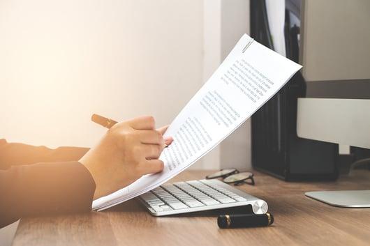 personne qui tient un document à la main avec un crayon