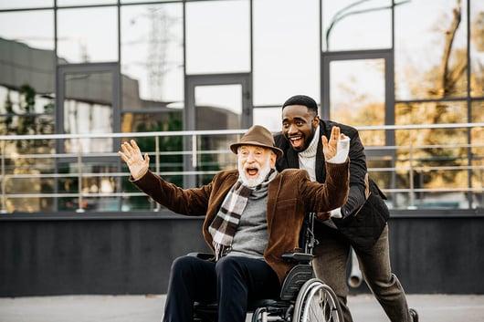 Hommes souriant promenant un homme en fauteuil roulant enthousiaste