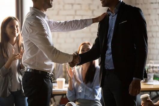 deux hommes se faisant une poignée de mains dans un bureau