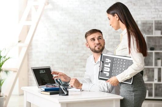 Employé utilisant un calendrier sur son écran au travail