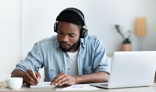 Homme afro-américain rédigeant dans un carnet devant son ordinateur