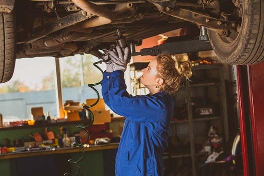 Mécanicienne réparant une voiture dans un garage