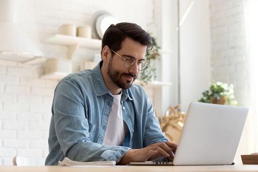 Jeune homme travaillant sur son ordinateur portable à la maison