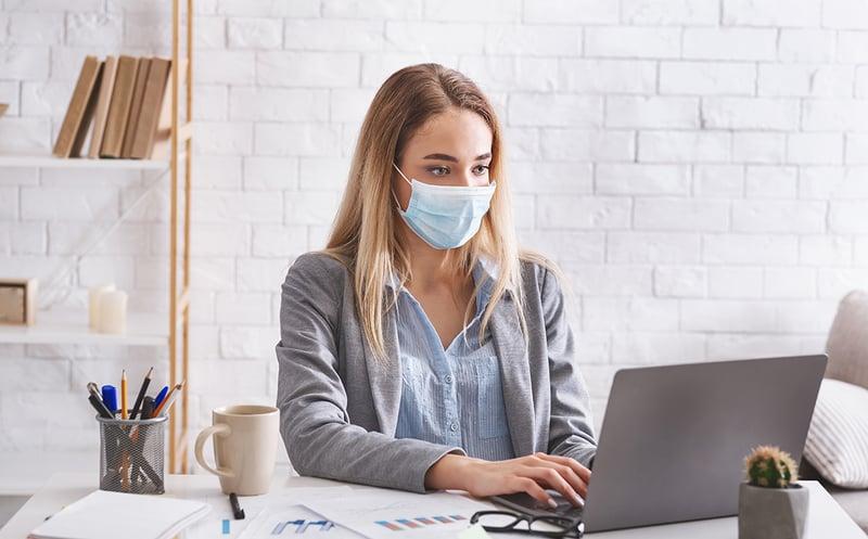 Jeune femme blonde portant un masque au travail