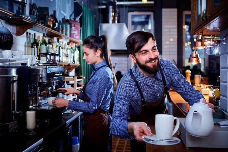 Un serveur et une serveuse préparant des boissons derrière le comptoir d'un bar