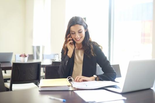 Femme au bureau au téléphone qui sourit