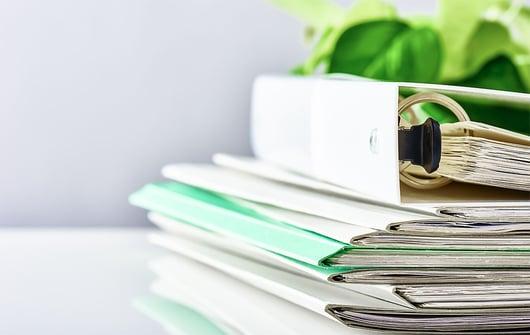 documents et classeurs posés sur une table
