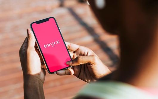 Femme avec son téléphone à la main avec l'application Bruce